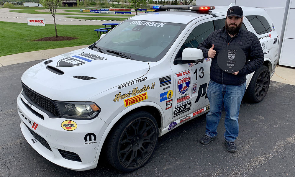 "David Carr, SRT vehicle performance dynamics engineer and co-driver of the Dodge Durango SRT Pursuit concept nicknamed ""Speed Trap"" shows off the trophy for winning the Truck/SUV class in the 2019 One Lap of America."